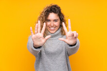 Young Blonde Woman With Curly Hair Wearing A Turtleneck Sweater Isolated On Yellow Background Counting Eight With Fingers