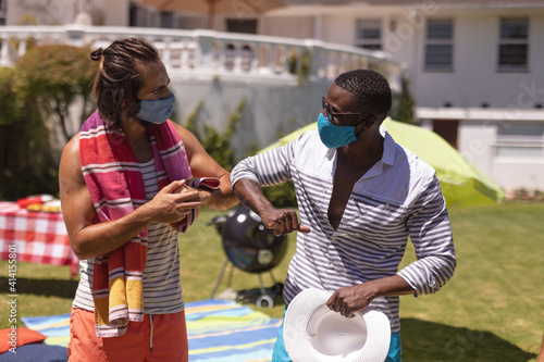 Two diverse male friends wearing face masks bumping elbows at a pool party