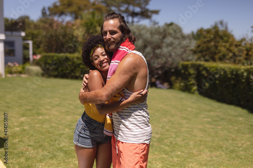 Portrait of two diverse male and female friends embracing at a pool party