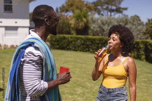 Two diverse male and female friends drinking and talking at a pool party