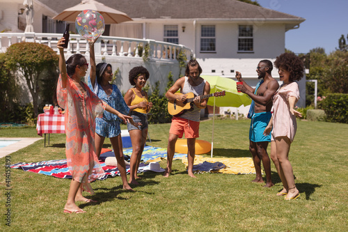 Diverse group of friends dancing and smiling at a pool party