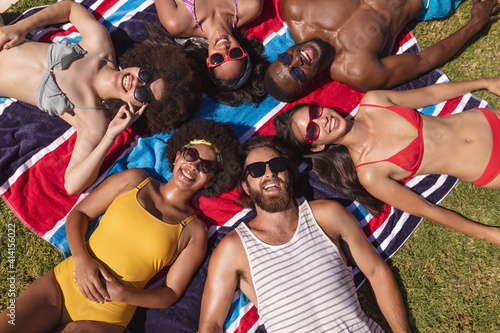 Diverse group of friends sunbathing together on a sunny day smiling