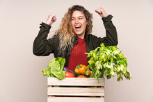 Farmer With Freshly Picked Vegetables In A Box Isolated On Beige Background Celebrating A Victory