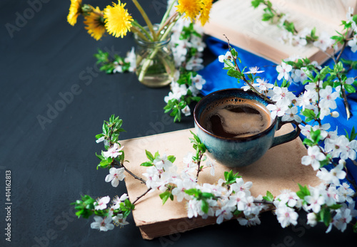 A cup of fragrant coffee, blooming spring cherry branches , the first yellow dandelions and an old book © pavelkant