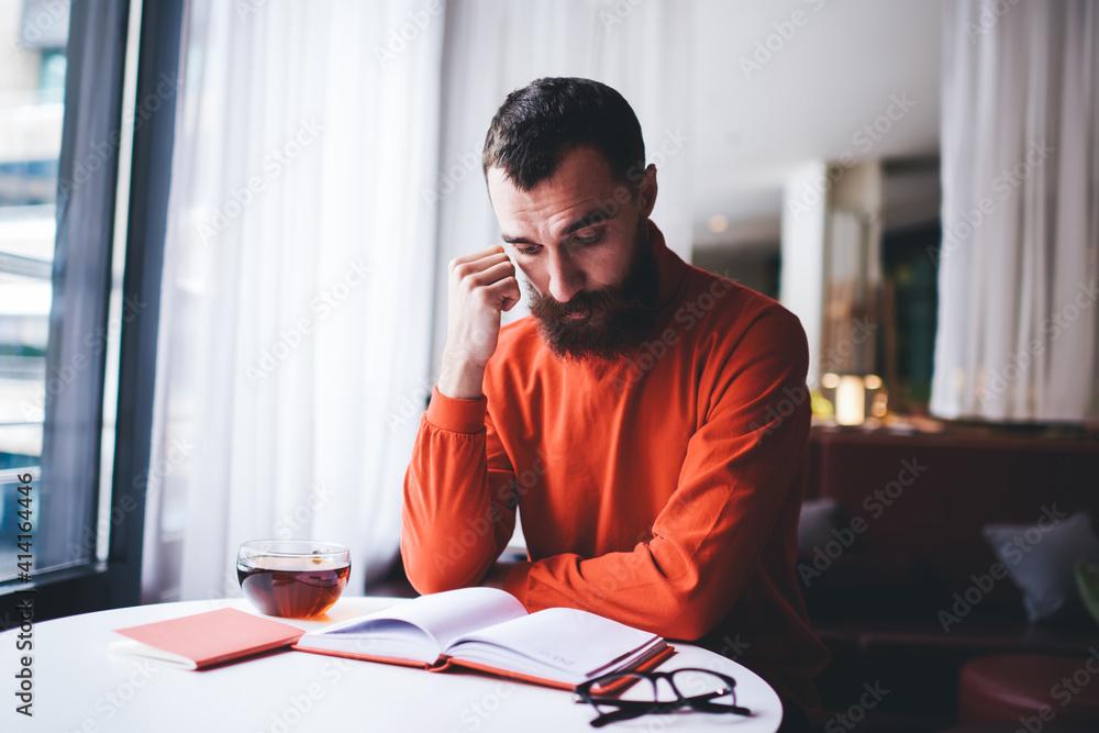 Fototapeta Focused man reading book in cafe