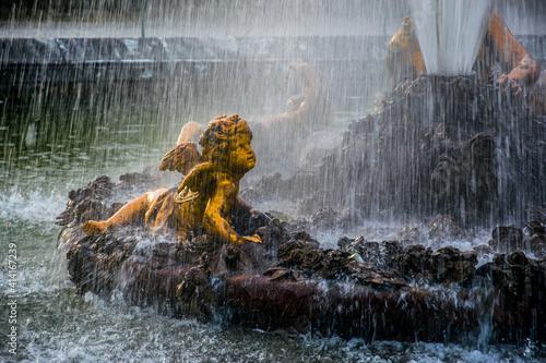 Fotografia Detalle del agua cayendo cerca de la estatua de un querubín en los jardines del