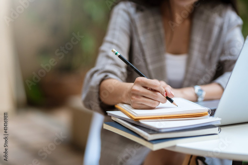 Close up of young woman hand taking notes with laptop at the table office.