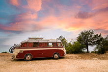A Red And White Vintage Van Is Parked On The Seafront Promenade In Sardinia During A Stunning Sunset. Beautiful Retro Passenger Van With A Dramatic Sky.