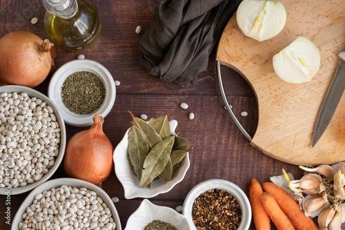 Fototapeta Traditional cuisine - raw beans and seasoning on wooden background obraz