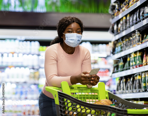 Shopping during coronavirus. Black woman in face mask buying food, checking grocery list on smartphone at supermarket © Prostock-studio