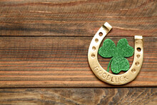 Golden Horseshoe And Decorative Clover Leaf On Wooden Table, Flat Lay With Space For Text. Saint Patrick's Day Celebration