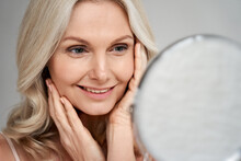 Happy 50s Middle Aged Woman Model Touching Face Skin Looking In Mirror. Smiling Mature Older Lady Pampering, Enjoying Healthy Skin Care, Aging Beauty, Skincare Treatment Cosmetic Products Concept.