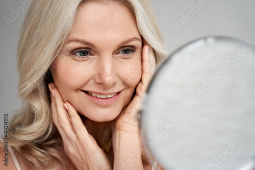 Canvastavla Happy 50s middle aged woman model touching face skin looking in mirror