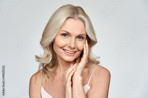 Foto Smiling happy attractive 50s middle aged blonde woman, older lady looking at camera advertising anti age face skin and body care treatment cosmetics isolated on white background
