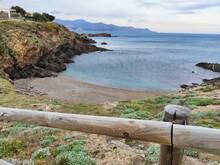 Mar En Calma, Con Montañas Al Fondo, Vista Desde El Camino De Ronda Junto A Una Pequeña Y Vacía Playa De Guijarros