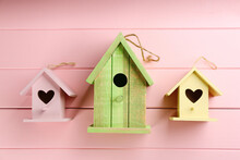 Three Different Bird Houses On Pink Wooden Background