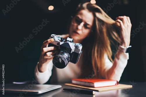 Obraz Young woman with analog photo camera at table - fototapety do salonu