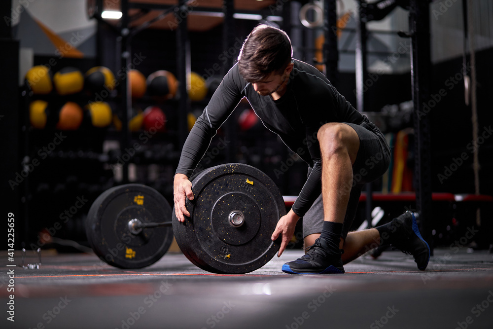 Fototapeta Athlete male adding weight plates on his barbell, young caucasian fit guy preparing for weightlifting workout at gym alone. bodybuilding concept