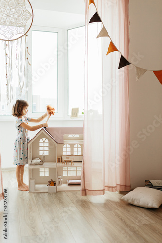 Fotografering Girl playing with doll house