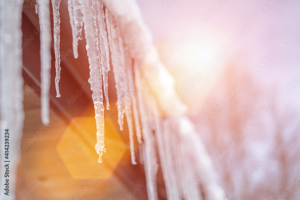 Fototapeta Spring bright sunlight shines on melting icicles hanging from roof