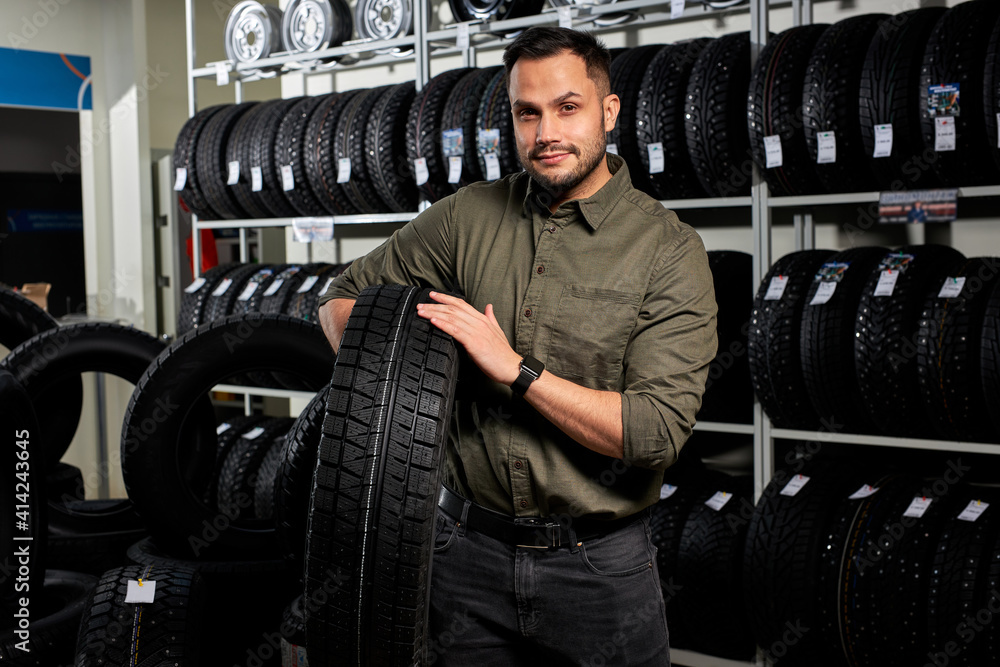 Fototapeta client guy stands with tires by rack of tires, he made choice, buy the best ones in auto service shop. portrait