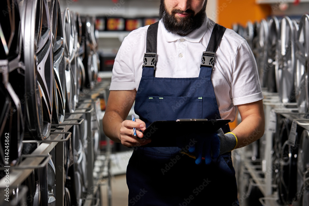 Fototapeta auto mechanic male with paper tablet in hands, writing characteristics, standing alone at work place, concentrated