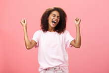 Amazed And Happy Triumphing African American Sportswoman Celebrating Victory Yelling From Awesome Exciting Feelings Closing Eyes Raising Fists Hight In Win Gesture Standing Over Pink Background