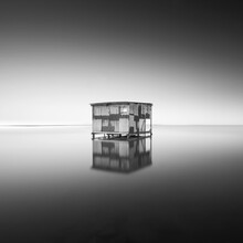 Greyscale Shot Of An Old Abandoned Hut With Reflection On The Ground