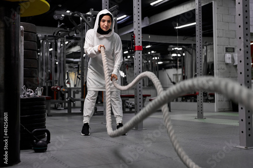 Fototapeta arabic female athlete doing crossfit workout with battle rope, wearing sportive hijab