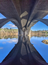 View Under An Concrete Arched Bridge With Reflections On The Water