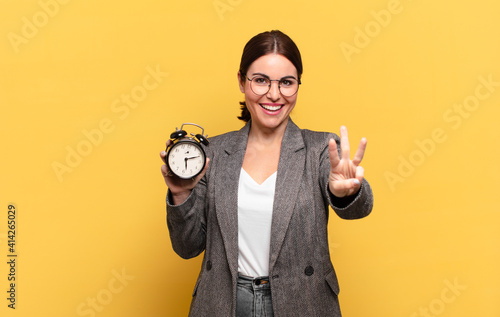 Obraz young pretty woman smiling and looking friendly, showing number three or third with hand forward, counting down - fototapety do salonu