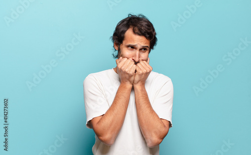 Photo young handsome indian man looking worried, anxious, stressed and afraid, biting