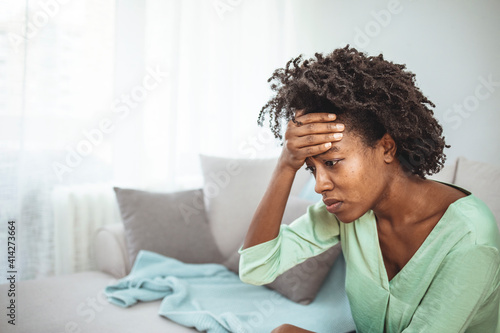 Canvas-taulu Close up african female sit on couch feels unhappy desperate thinking about pers