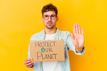 Young Caucasian Man Holding A Protect Our Planet Placard Isolated Standing With Outstretched Hand Showing Stop Sign, Preventing You.