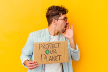 Young Caucasian Man Holding A Protect Our Planet Placard Isolated Shouting And Holding Palm Near Opened Mouth.
