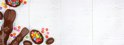 Easter candy, chocolate bunnies and eggs. Above view corner border against a white wood banner background. Copy space. © Jenifoto
