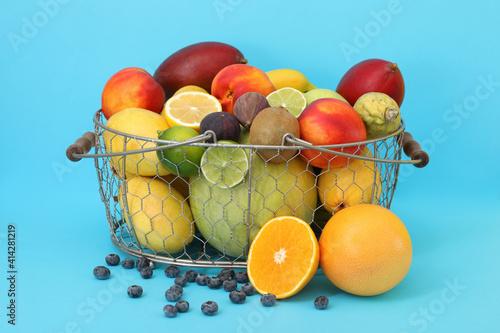 Assortment of fresh exotic fruits in basket on light blue background