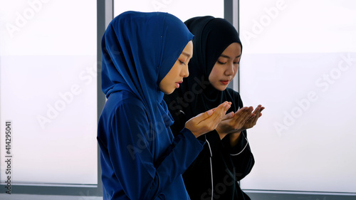 Slika na platnu Two Asian Muslim young women in traditional hijab are praying glorify Allah and practicing the Islamic faith in mosque