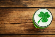 Top View Of Beer With Clover Leaf On Wooden Table, Space For Text. St Patrick's Day Celebration