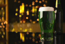 Glass Of Green Beer On Black Table Against Blurred Lights, Space For Text. St Patrick's Day Celebration