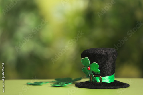 Fototapeta Leprechaun hat and clover leaves on table against blurred background, space for text. St Patrick's Day celebration obraz