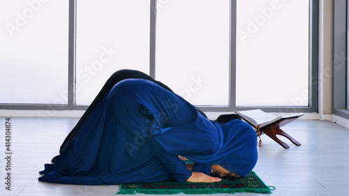 Fotografija Two Asian Muslim young women in traditional hijab are praying glorify Allah and practicing the Islamic faith in mosque