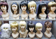 A Row Of Various Female Wigs On Mannequin Heads In A Shop Window