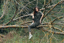 A Woman On A Broken Tree In Sneakers And A Green Overalls