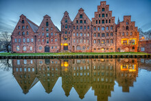 The Historic Salzspeicher Reflecting In The Trave River At Dawn, Seen In Luebeck, Germany