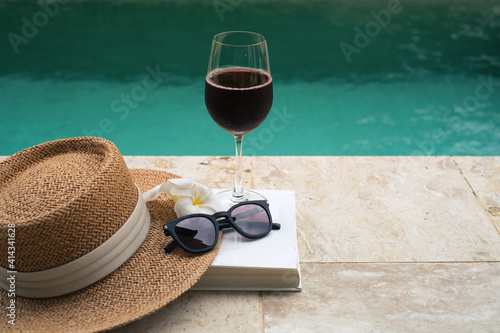 Canvas Print Brown panama hat and a glass of red wine on book at the side of swimming pool