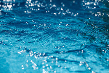 Close-up Of Blue Water In The Pool. Side View. Bokeh Light Background In The Pool.