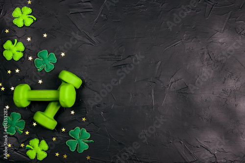 Valokuva Green dumbbell with decorative clover leaves and gold stars on black background