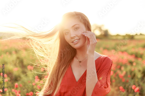 Obraz Gentle blonde long-haired woman with perfect smile posing on poppy field in warm summer sunset. - fototapety do salonu