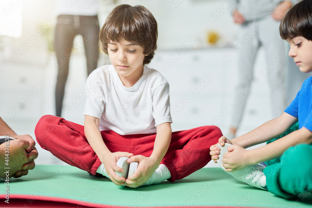 Fototapeta Family workout. Two adorable little hispanic boys sitting in yoga pose on a mat while having morning workout with parents at home